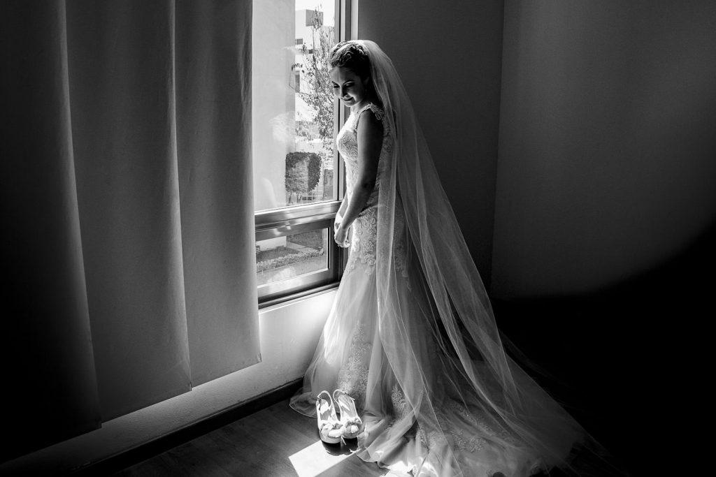 La novia junto a un ventana con luz natural blanco y negro