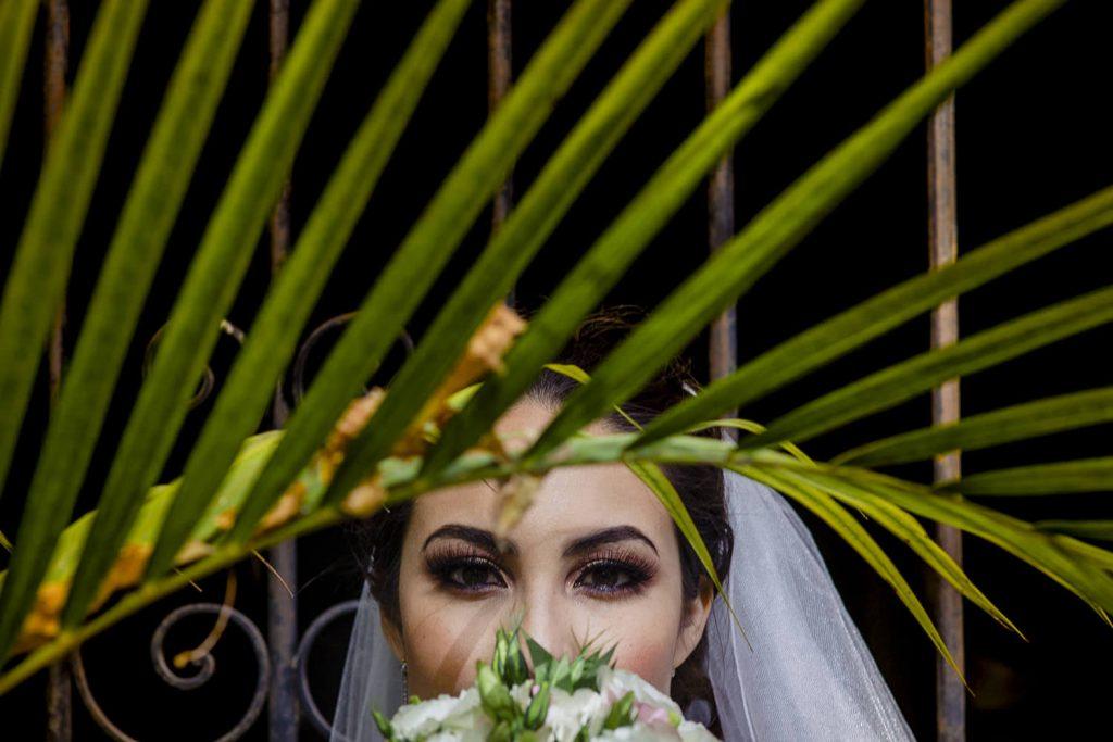 Retrato espectacular de la novia detras de una hojas