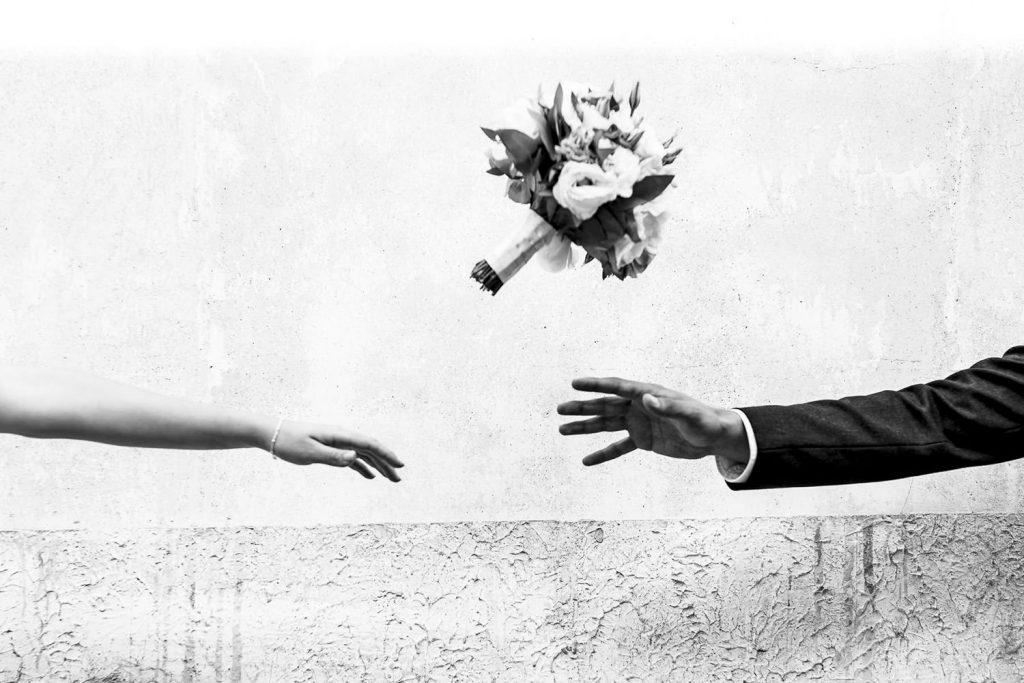 Manos de los novios y ramo de novia en blanco y negro