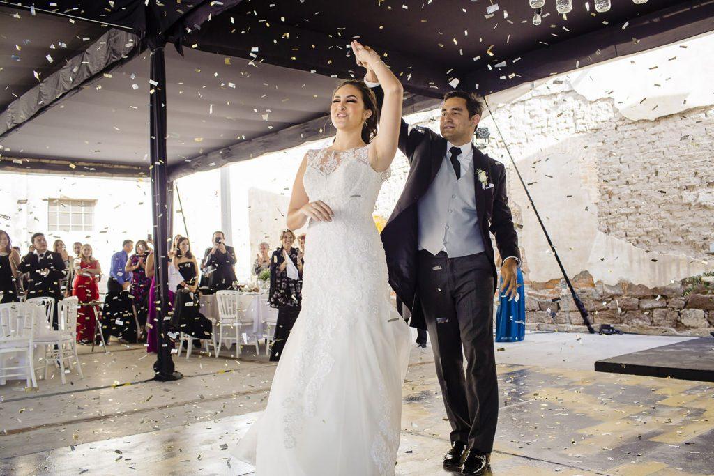 Los novios entran a la boda de la mano con papelitos metalicos