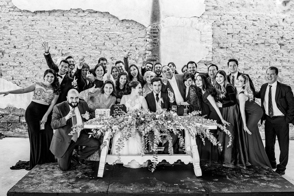 Invitados felices posando en la foto familiar de la boda