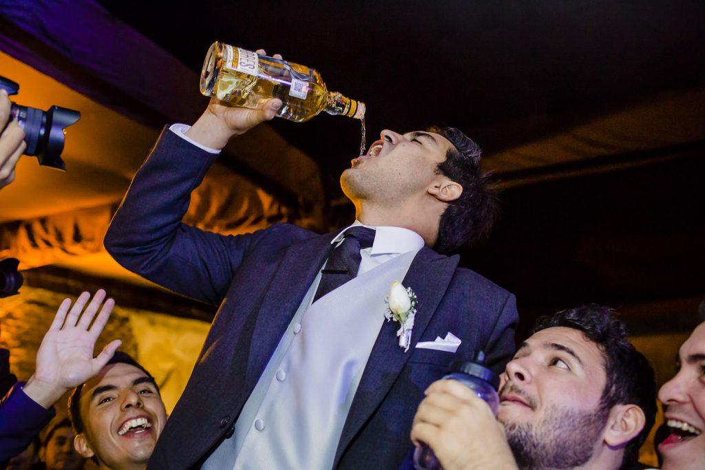 El novio festejando con sus amigos y un trago de tequila