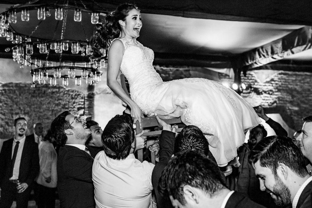 La novia es cargada por sus amigos en una silla